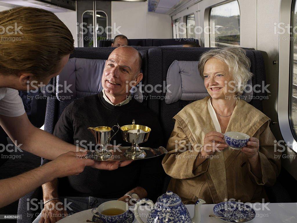 Waiter serving couple on train stock photo