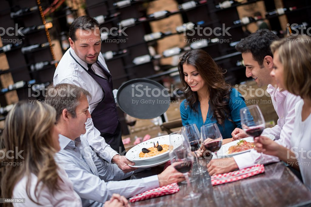 Waiter serving food at a restaurant stock photo