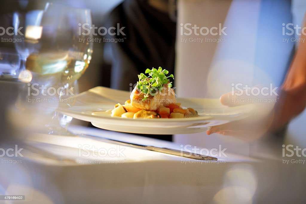 Waiter serving meal at table stock photo