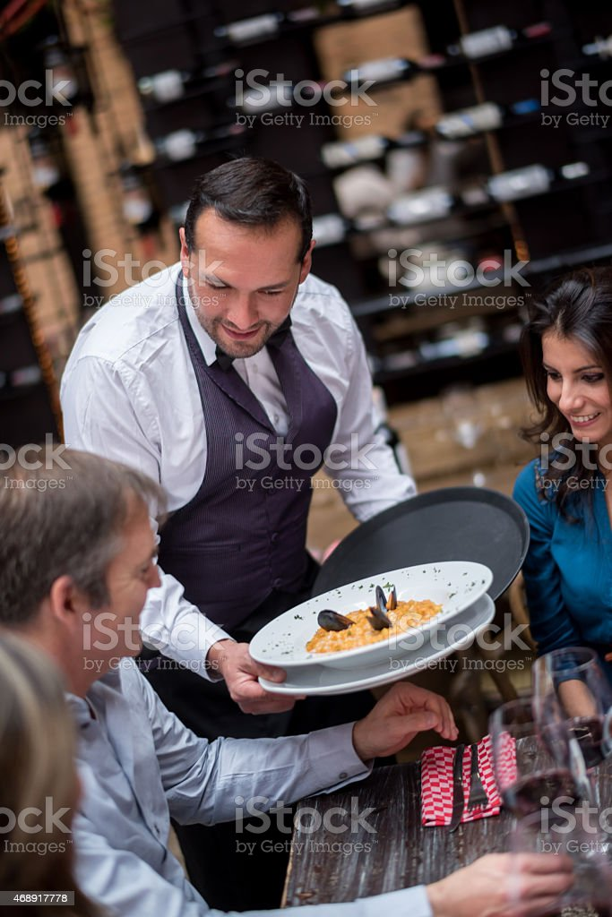 Waiter serving plates at a restaurant stock photo