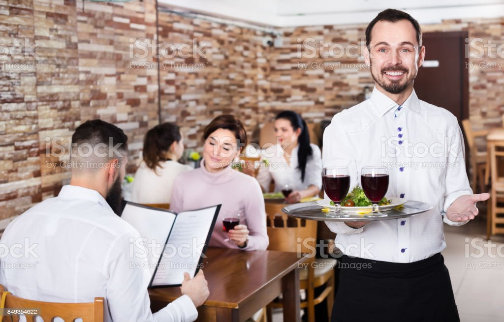 Waiter serving restaurant guests stock photo