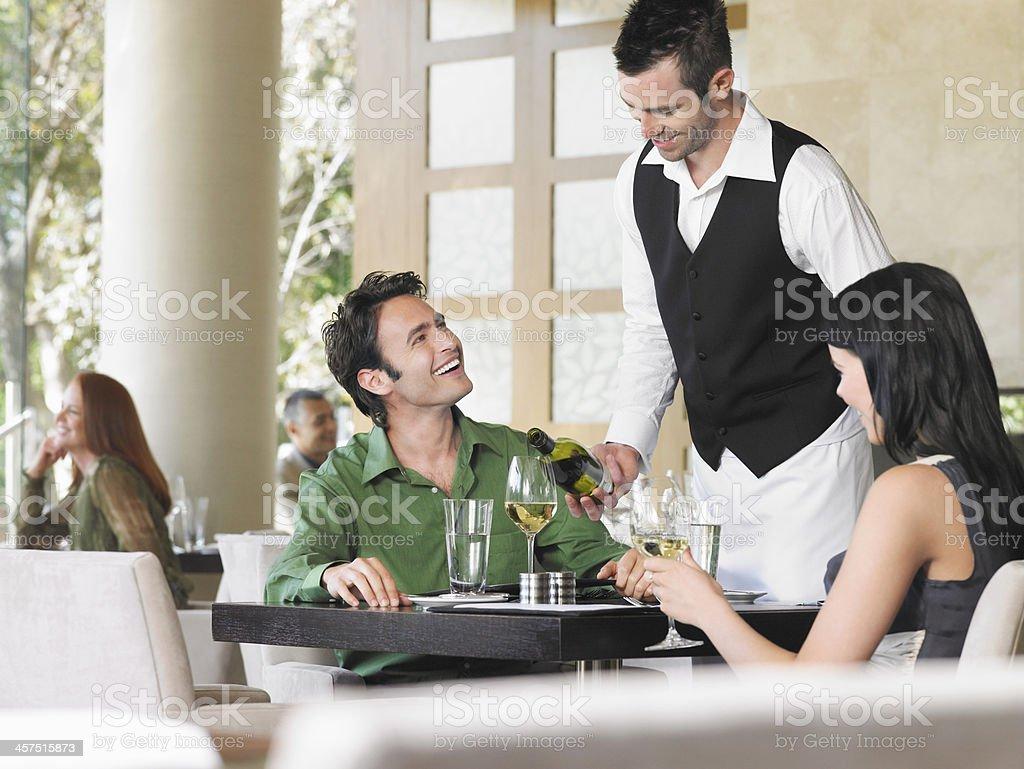 Waiter Serving Wine To Couple stock photo