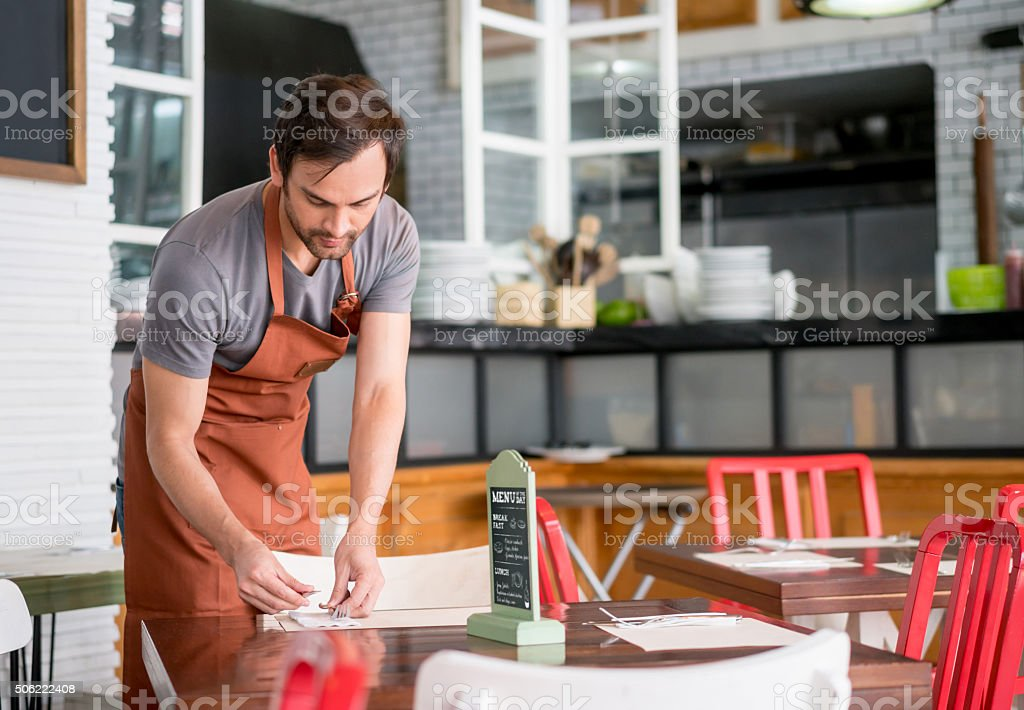 Waiter setting the table at a restaurant stock photo