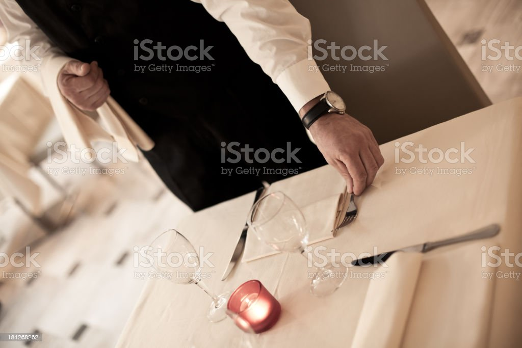 Waiter Setting the Table for Elegant Dinner stock photo