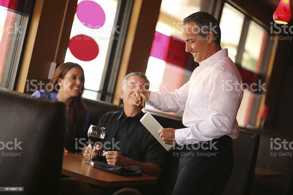 Waiter Swiping Credit Card With Digital Tablet stock photo