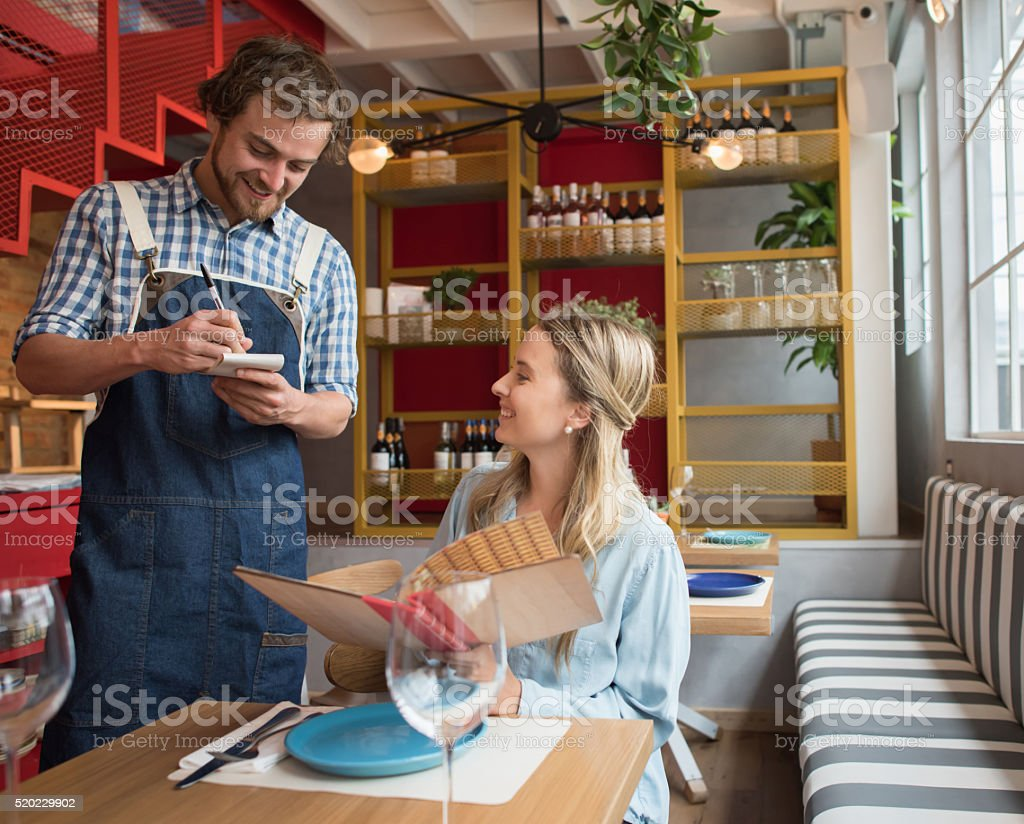 Waiter taking an order at a restaurant stock photo