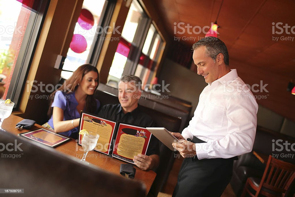 Waiter Taking Order From Couple At Restaurant royalty-free stock photo