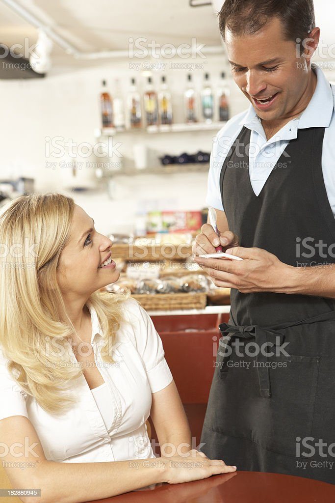 Waiter Taking Order From Customer In Coffee Shop royalty-free stock photo