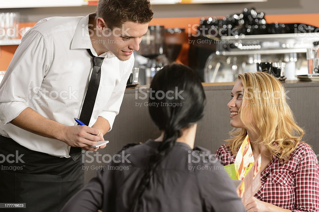 Waiter taking orders from young woman customer stock photo