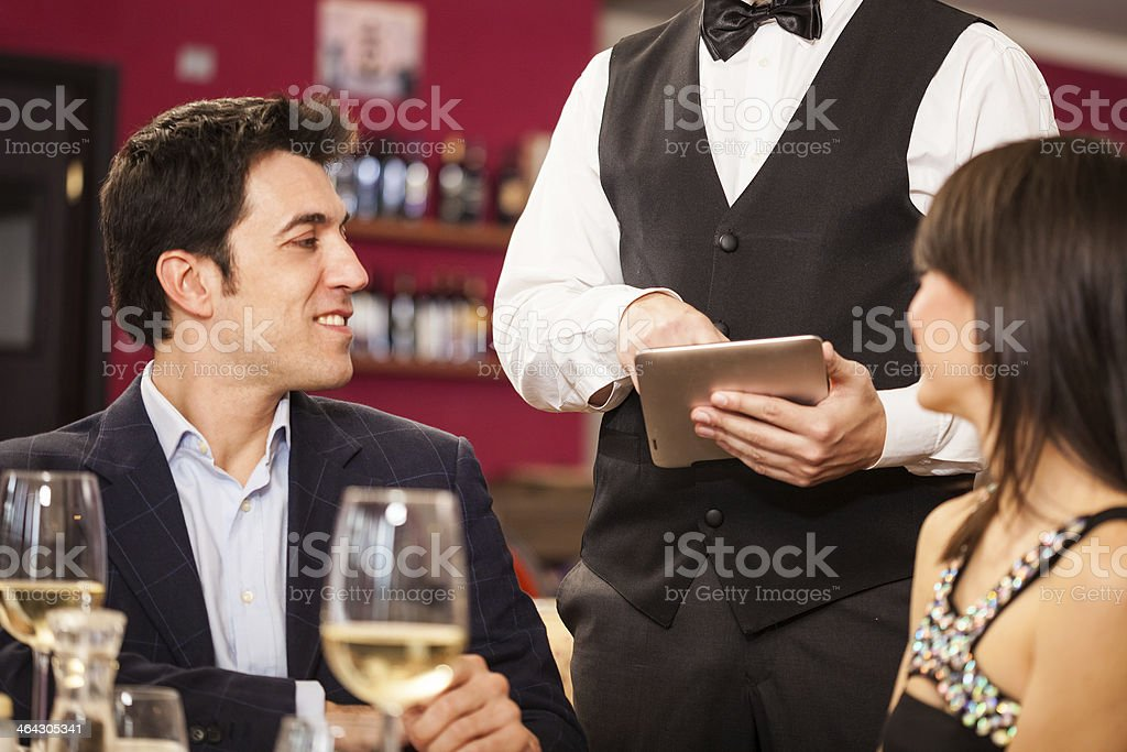 Waiter using a digital tablet royalty-free stock photo