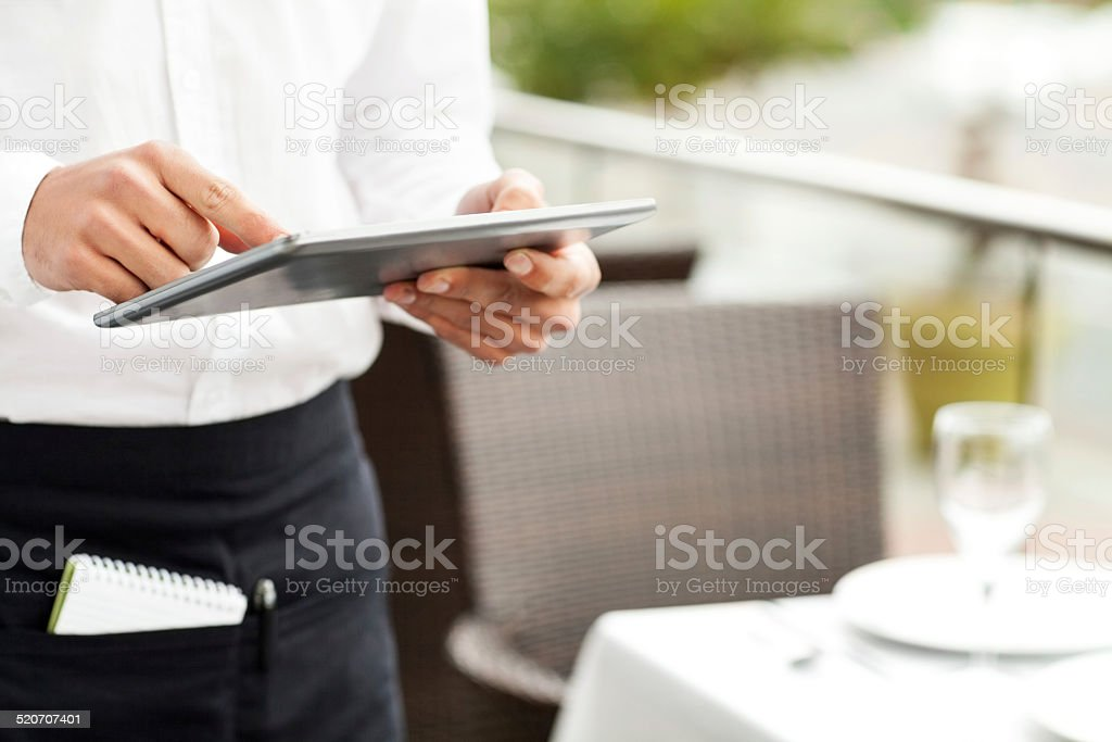 Waiter Using Digital Tablet To Take Order In Restaurant stock photo