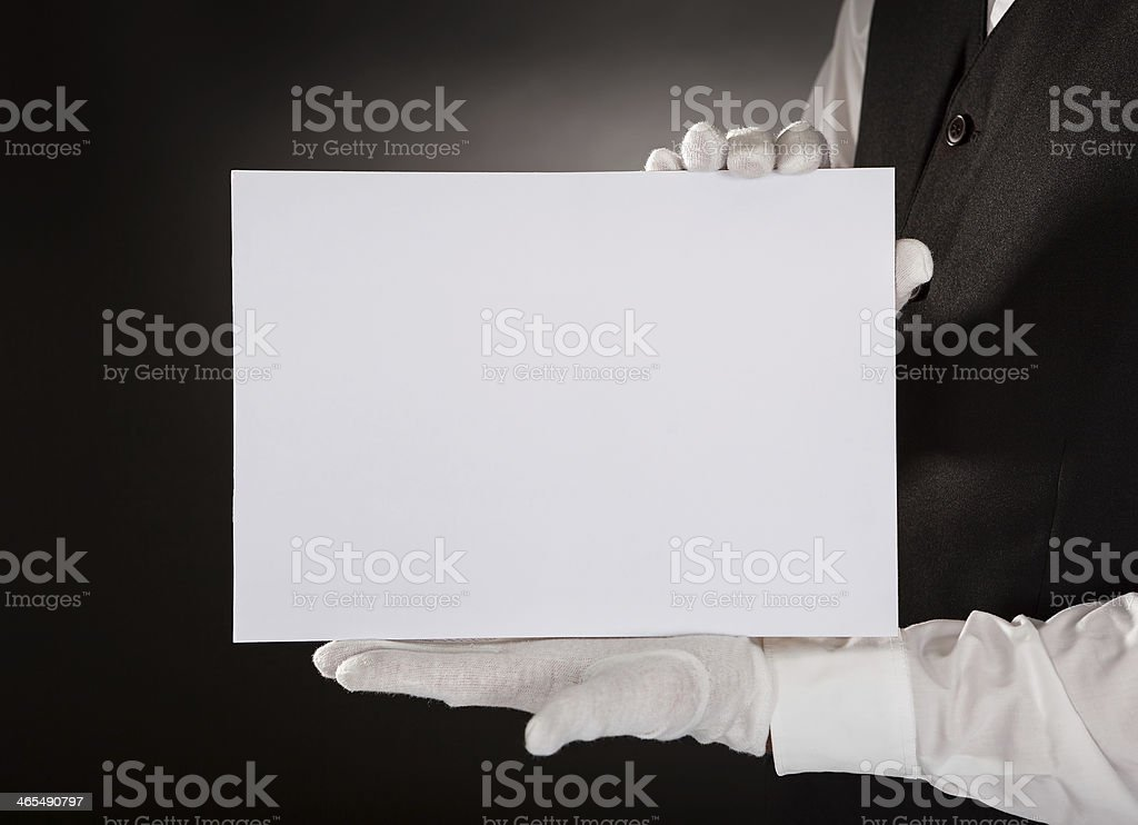 Waiter wearing white gloves holding a blank placard stock photo
