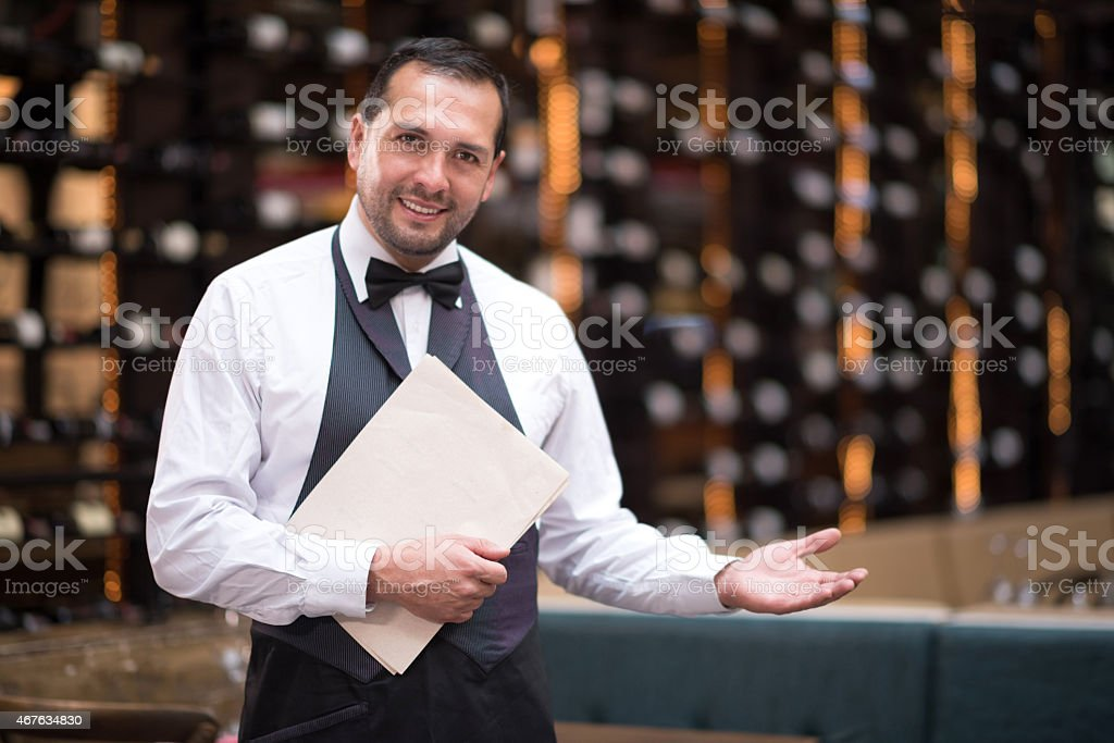 Waiter welcoming people to a restaurant stock photo