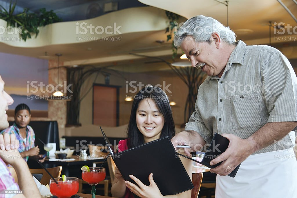 Waiter With Couple in Restaurant royalty-free stock photo