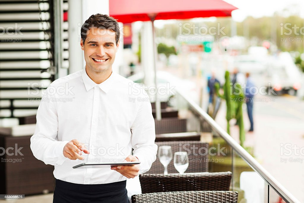 Waiter With Digital Tablet Smiling In Restaurant stock photo