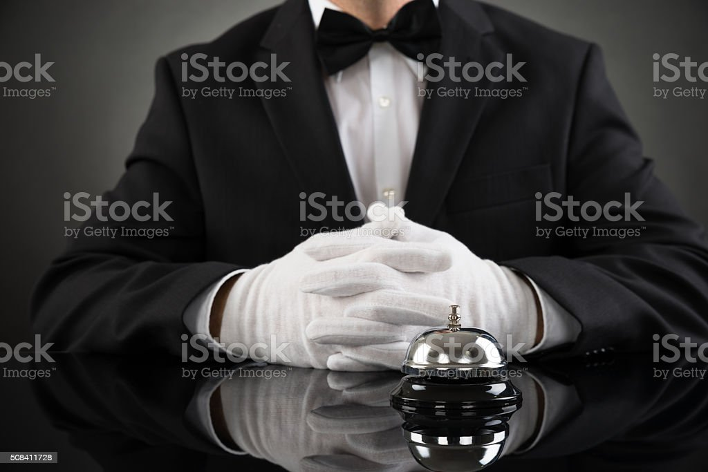 Waiter With Service Bell At Desk stock photo