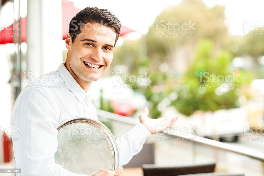 Waiter With Serving Tray Welcoming In Restaurant royalty-free stock photo