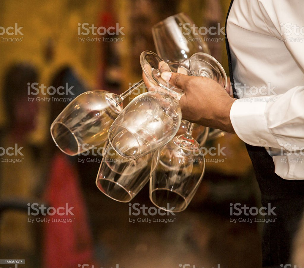 Waiter with several wine cups on his hand. royalty-free stock photo