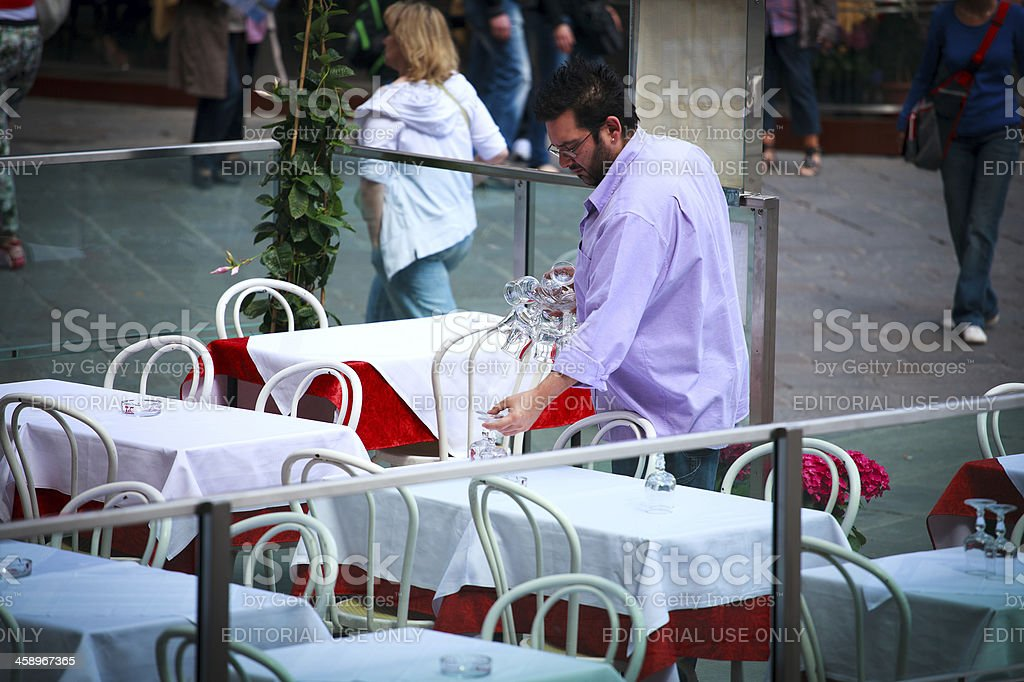 Waiter with stemwares is servesing a table stock photo