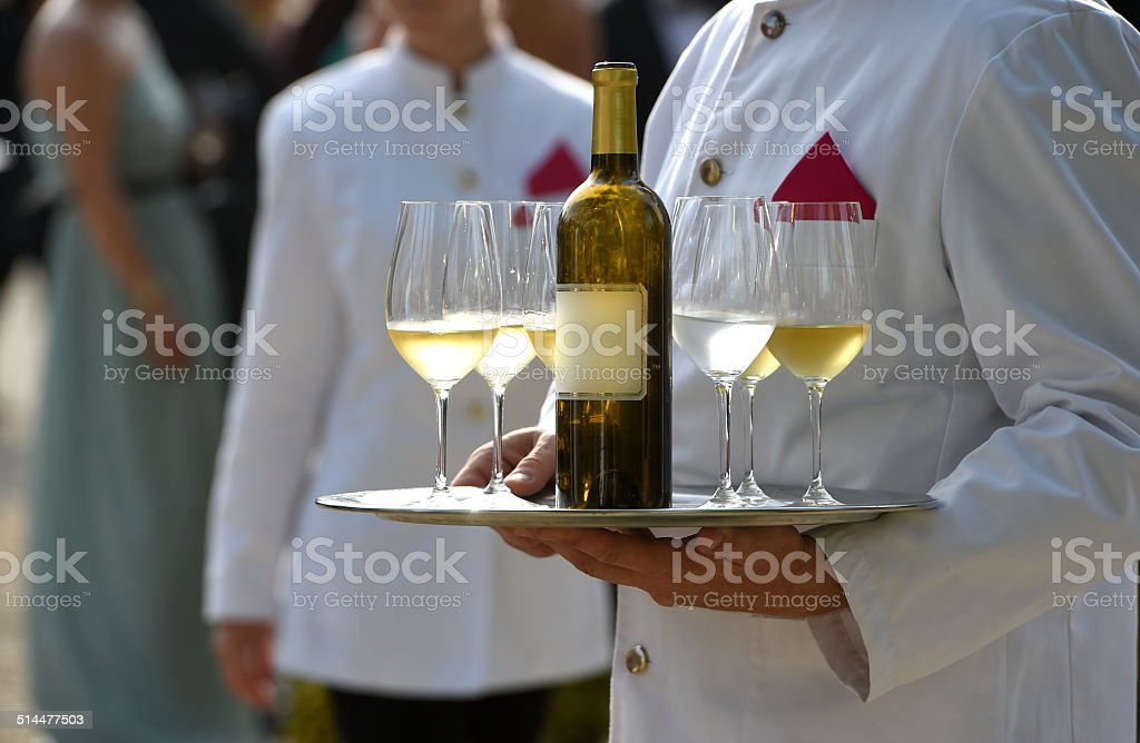 Waiters are serving vine at a wedding outdoor party stock photo
