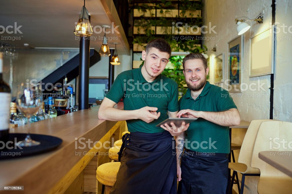Waiters, bartenders barista rest with the tablet in a break cafe stock photo
