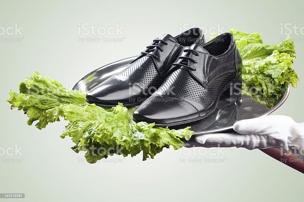 Waiter's hands holding pair of male shoes royalty-free stock photo