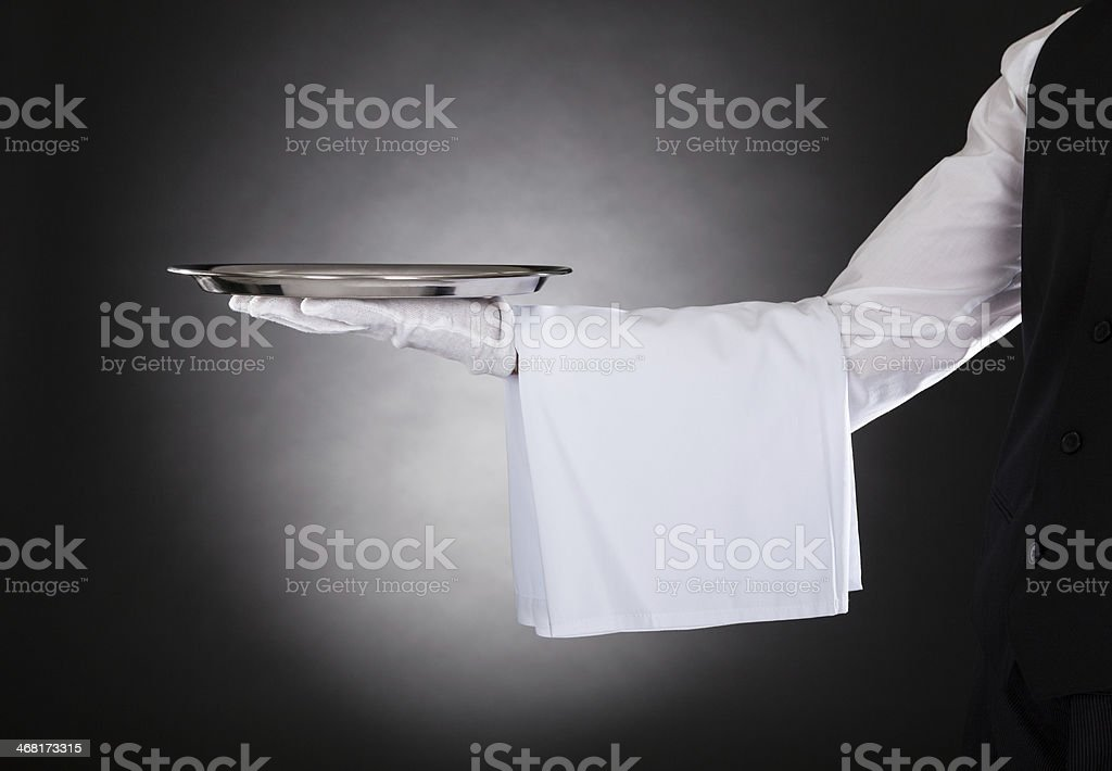 Waiter's outstretched arm holding a silver platter stock photo
