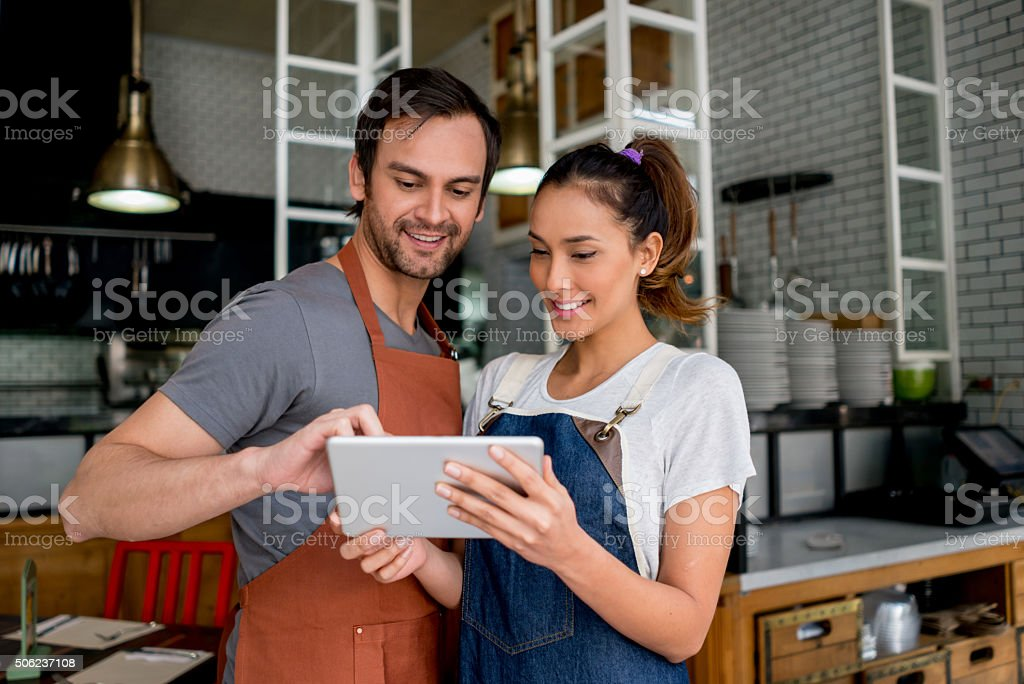 Waiters using technology at a restaurant stock photo
