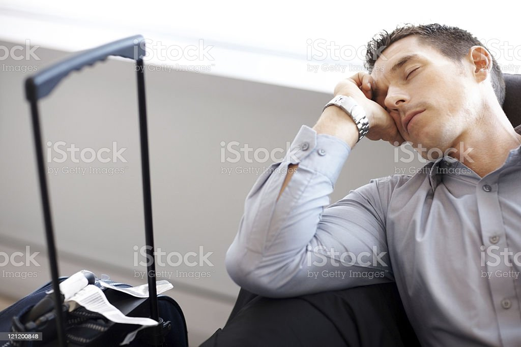 Waiting for flight - Young man sleeping at airport lounge royalty-free stock photo