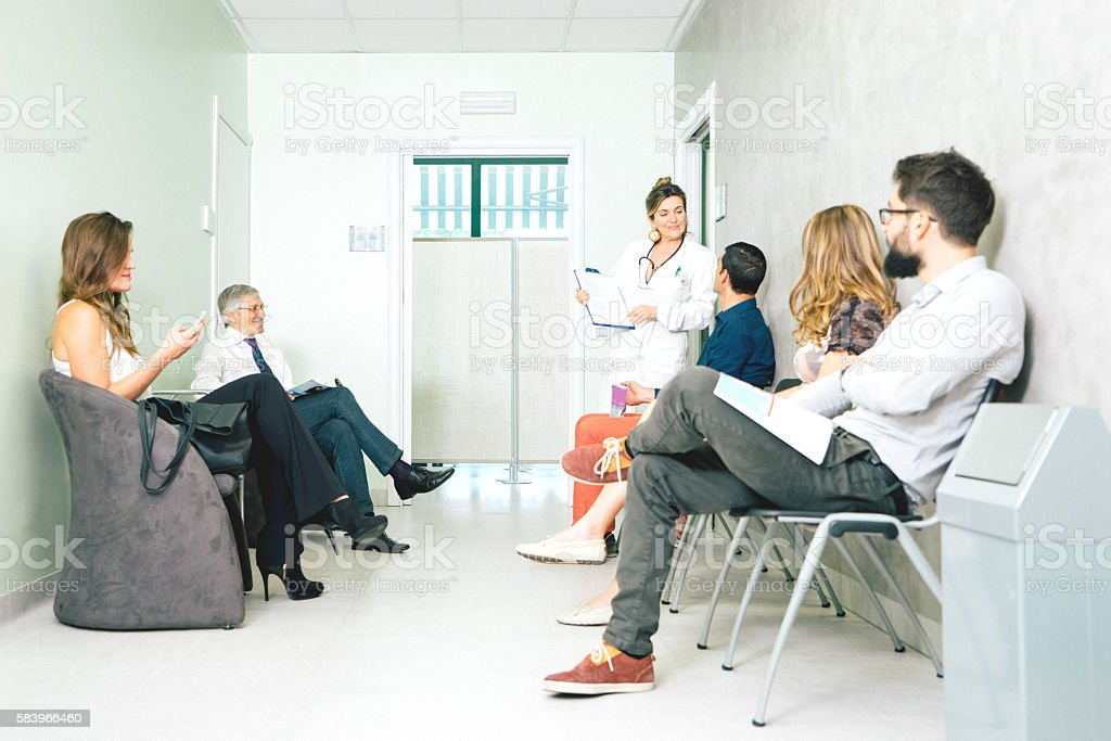 Waiting Room, Mature Female Doctor Talking To A Patient stock photo
