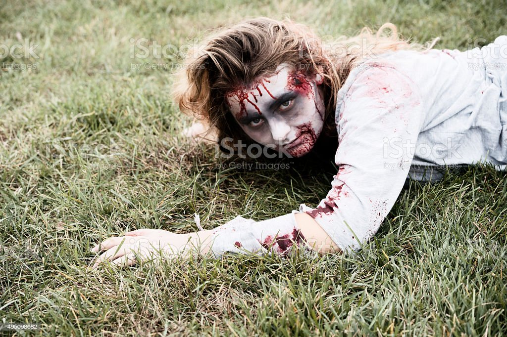 Waiting Zombie lying in grass stock photo