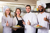 Waitress and cooking team in restaurant