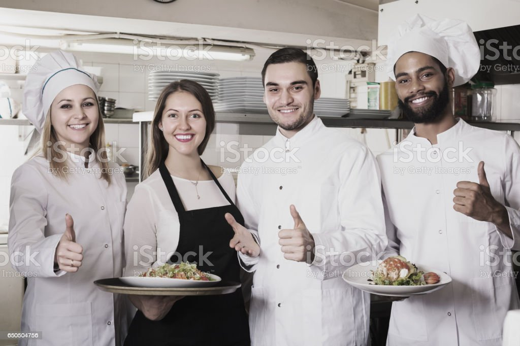 Waitress and cooking team in restaurant stock photo