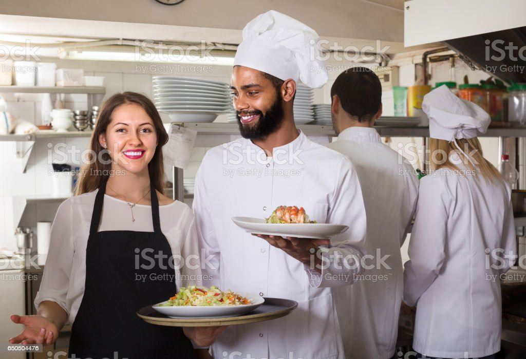 Waitress and crew of professional cooks posing at restaurant stock photo