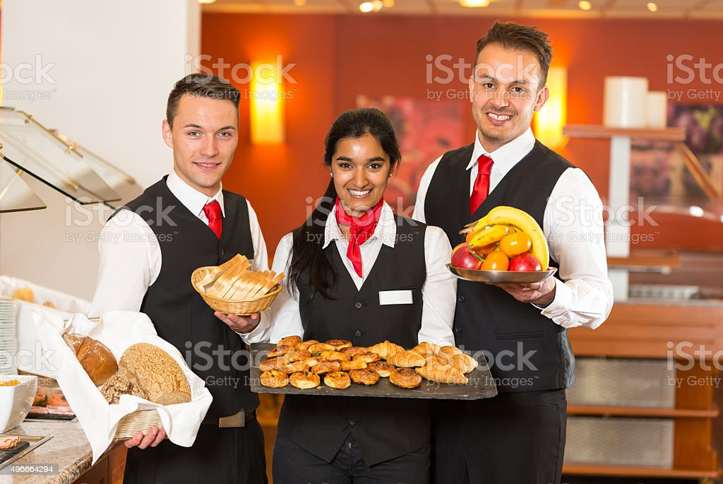 Waitress and waiters posing with food at buffet in restaurant stock photo