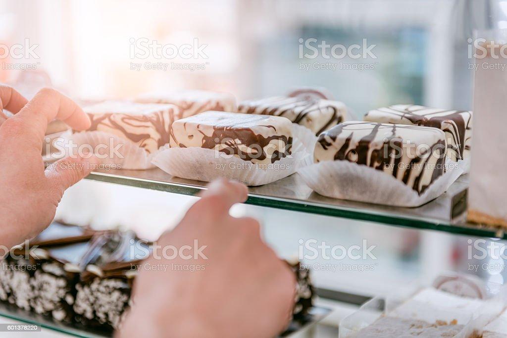 Waitress arranging cake at display cabinet stock photo