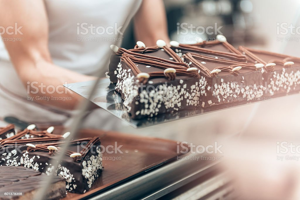 Waitress arranging cake at display cabinet stock photo
