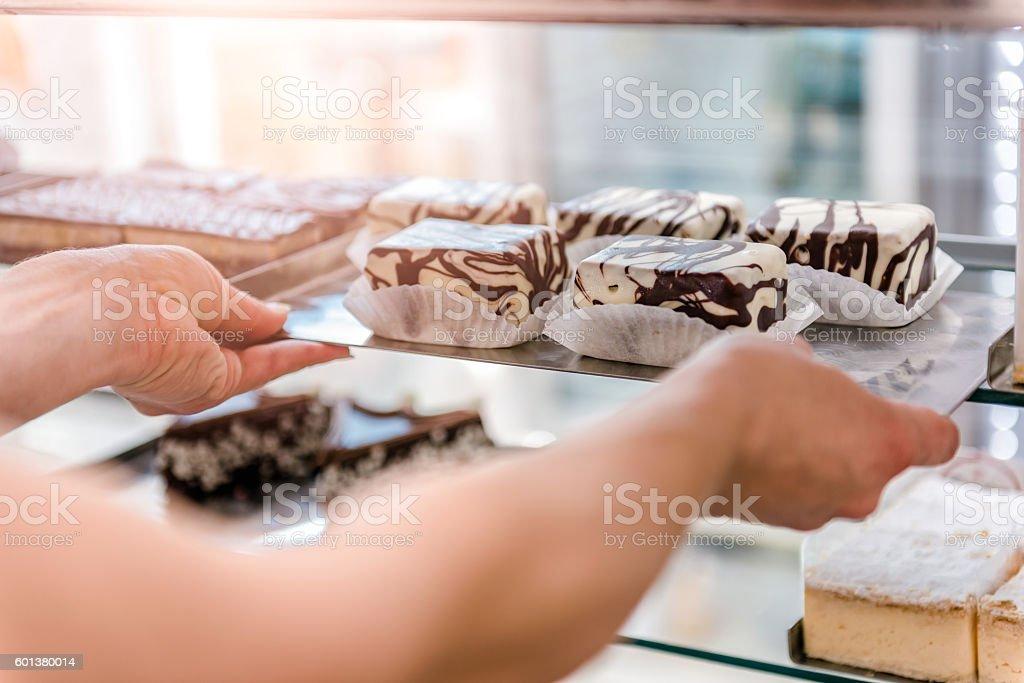 Waitress arranging cakes stock photo