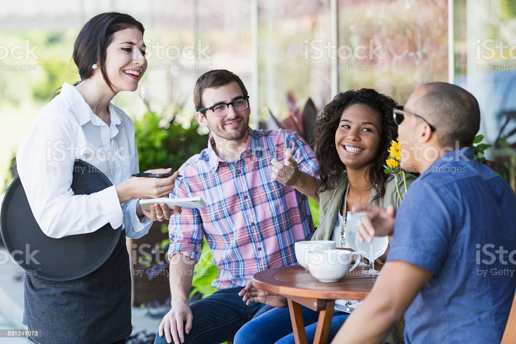 Waitress at sidewalk cafe with customers stock photo