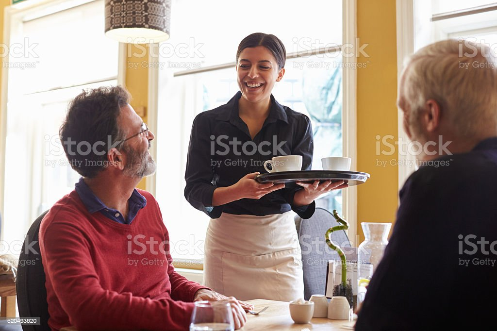 Waitress bringing coffees to a male couple at a restaurant stock photo