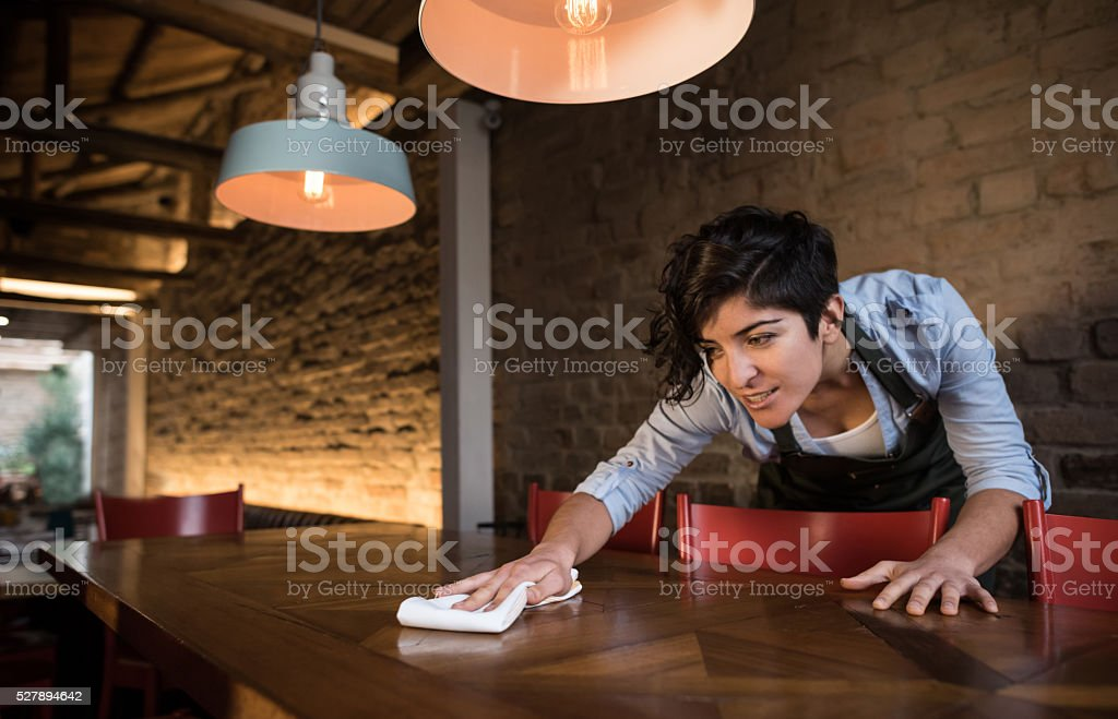 Waitress cleaning a table at a restaurant stock photo