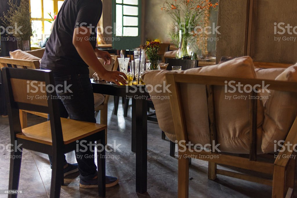 Waitress cleaning up the table after customers left stock photo