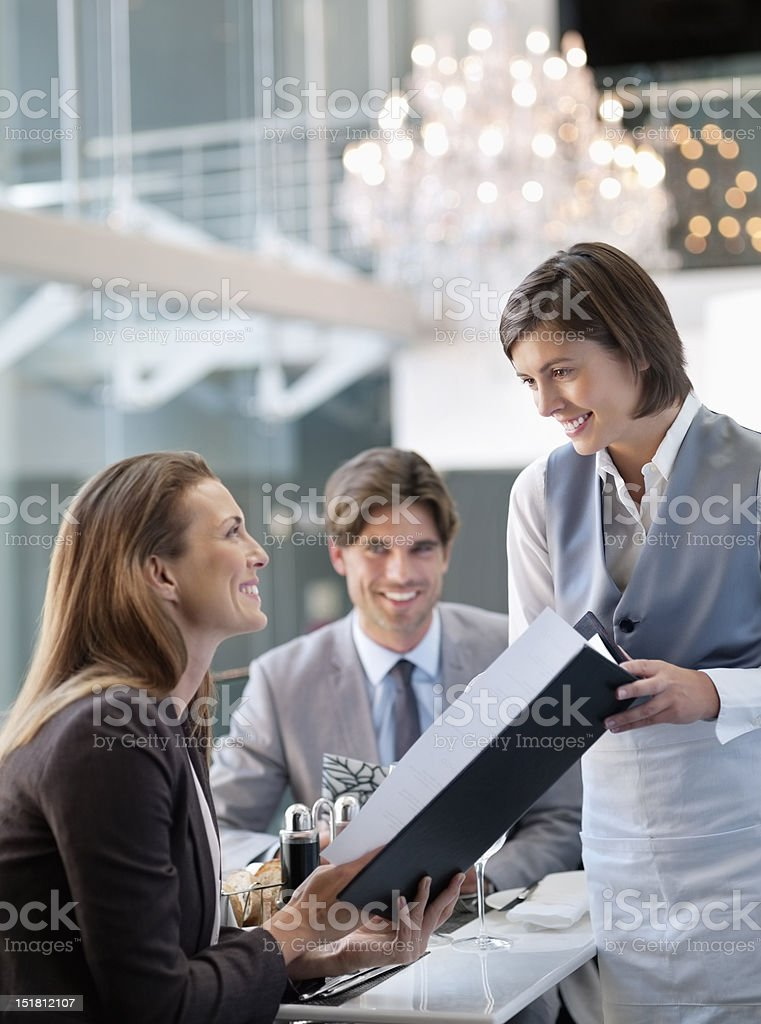 Waitress giving menu to woman in restaurant stock photo