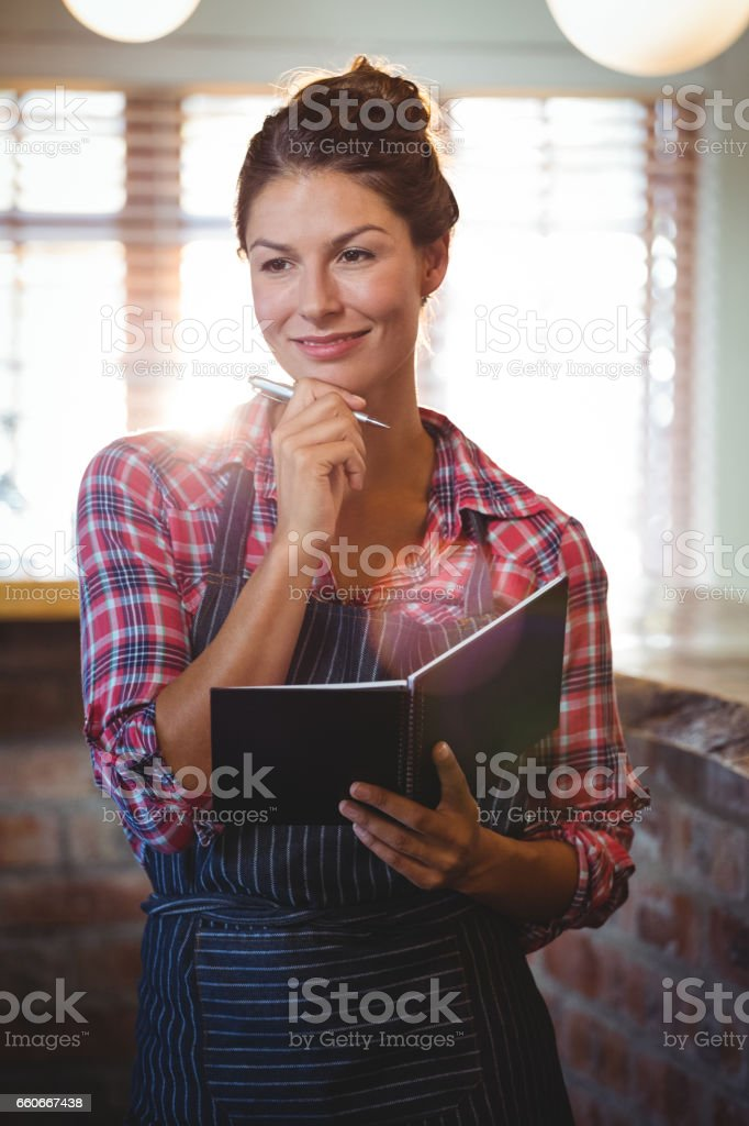 Waitress holding a pen and a book stock photo