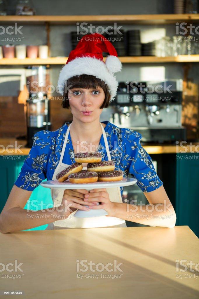 Waitress holding a tray of doughnuts stock photo