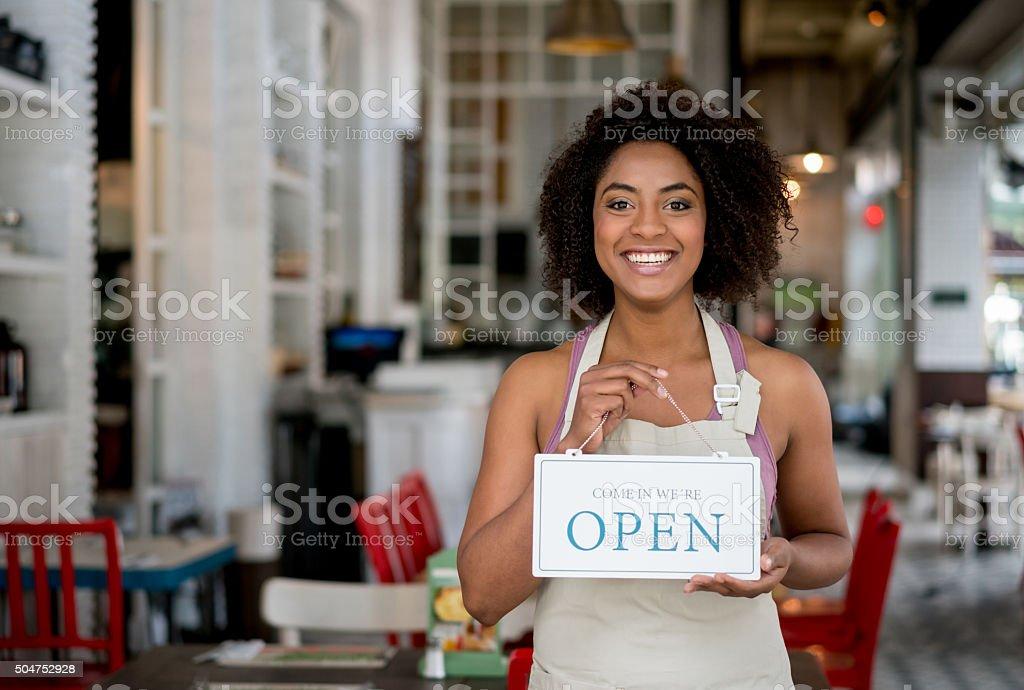 Waitress holding an open sign at a restaurant stock photo