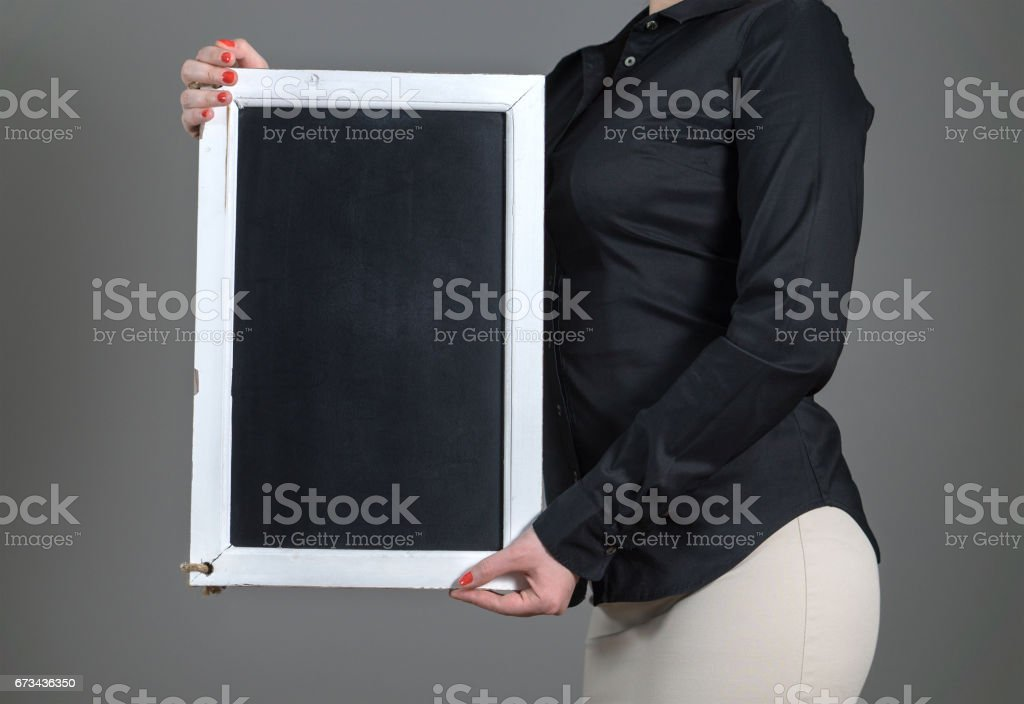 Waitress holding chalkboard vertically on a dark gray background. Free blank empty copy space for text, menu or specials. Waiter in a restaurant or business person. stock photo