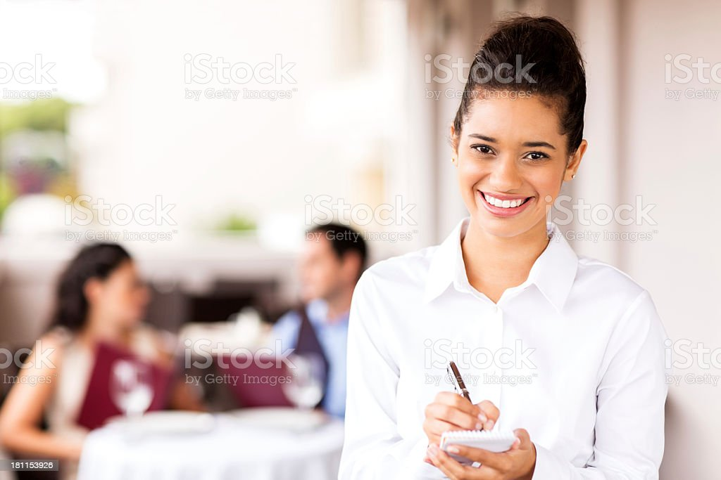 Waitress Holding Order Pad And Pen With Couple In Background royalty-free stock photo