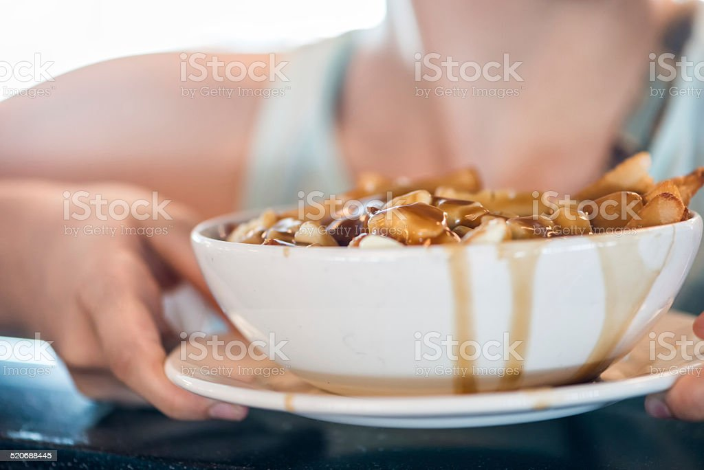 Waitress Holding Serving of Poutine in a Restaurant stock photo