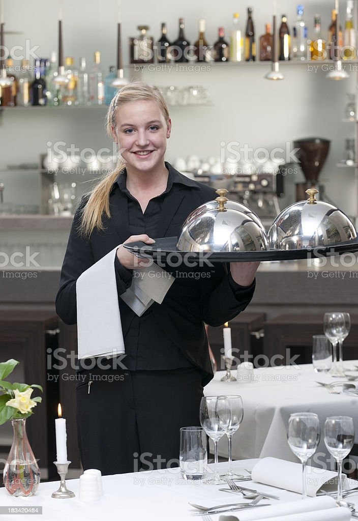 waitress holding serving tray in restaurant stock photo